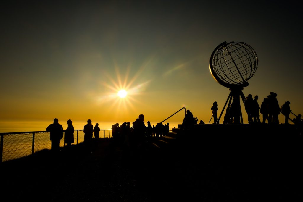silhouette of people standing on the beach during sunset
