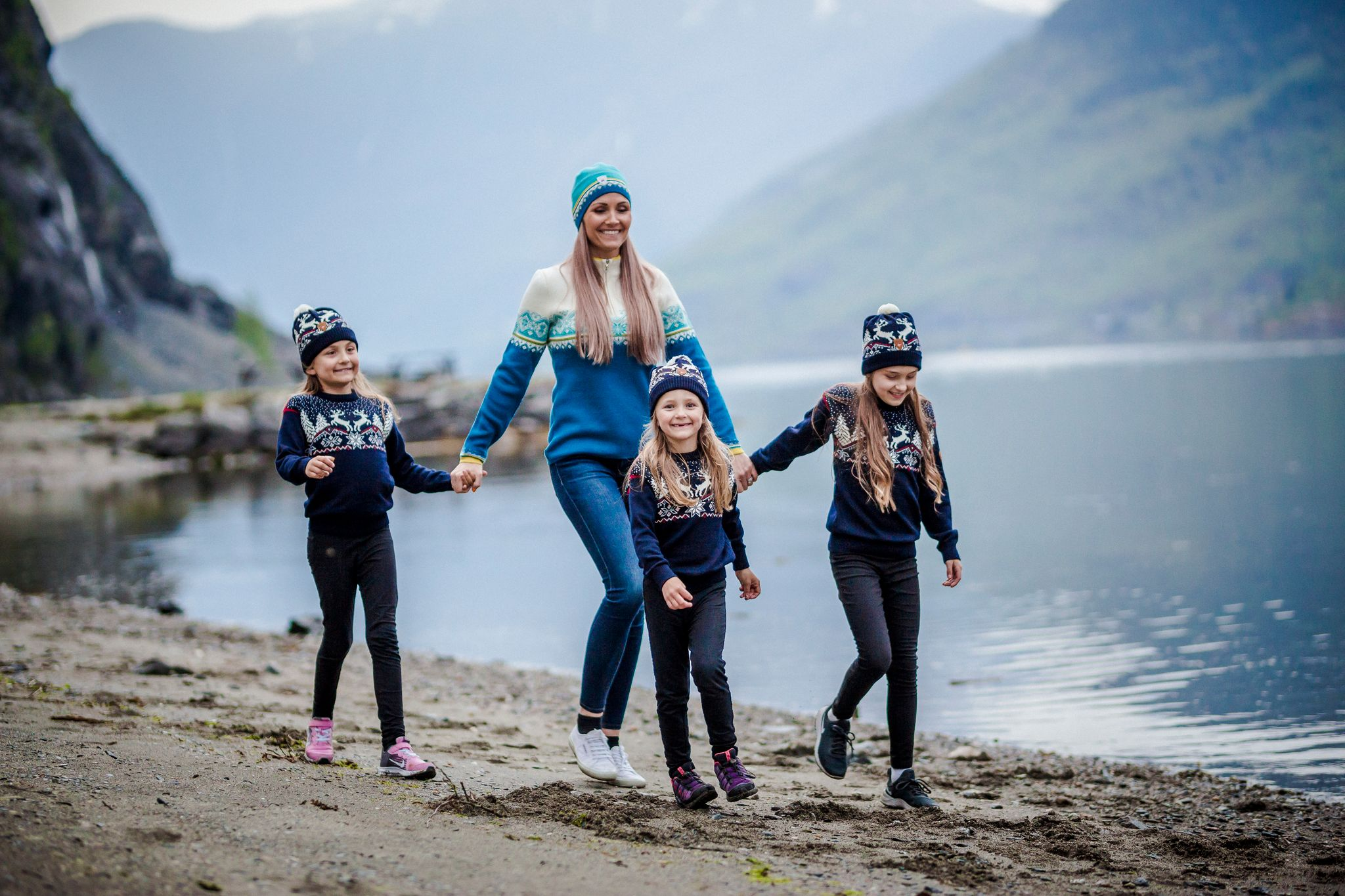 Family walking by the fjords in wool clothing